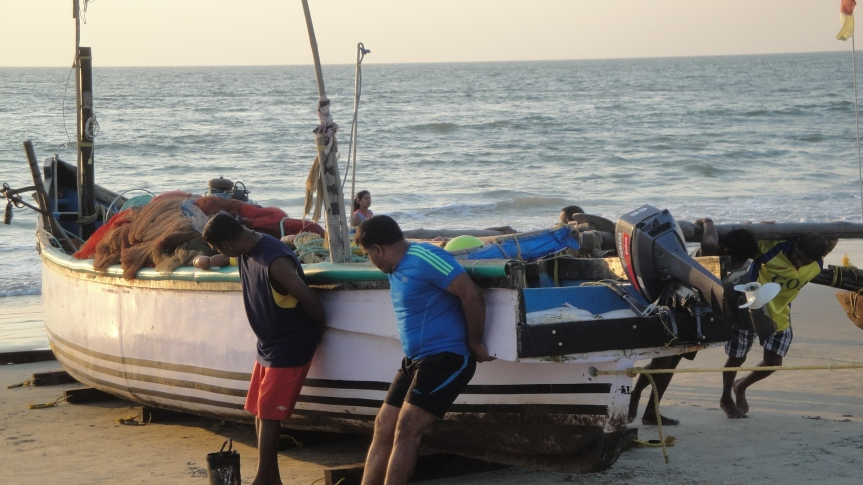Fishermen pulling boat out of sea